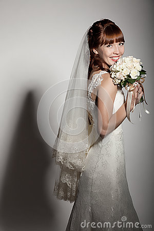 A beautyful bride holding her bouquet from roses and smiling