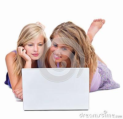 Beaux jeunes amis regardant l ordinateur portatif