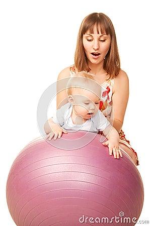 Bebé con la madre en bola de la aptitud