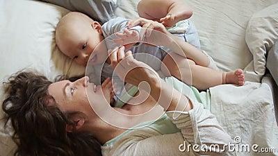 Bebé y mamá felices en mirada de la cama en uno a Buena mañana de la familia, el día de madre almacen de metraje de vídeo