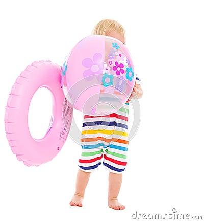 Bebê com o anel inflável que esconde atrás da esfera