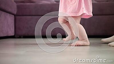 Bebê que executa primeiras etapas em sua vida Caminhada de aprendizagem infantil Pés pequenos da etapa video estoque