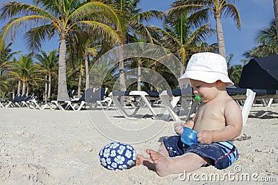 Bebê que joga na praia tropical