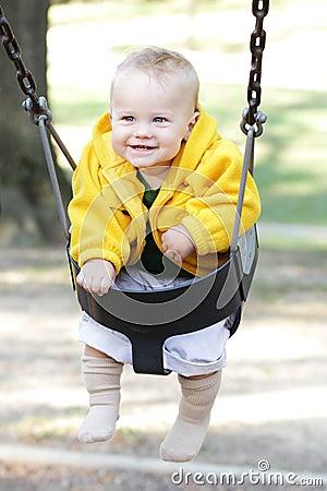 Bebé feliz en el oscilación