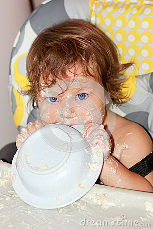 Bebê que come o yogurt e a face sujada