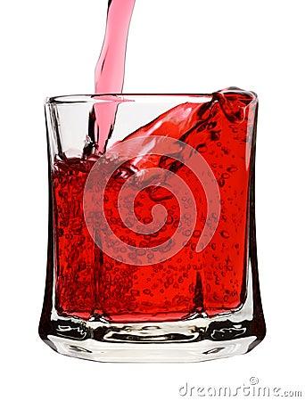 A bebida vermelha está sendo derramada no vidro