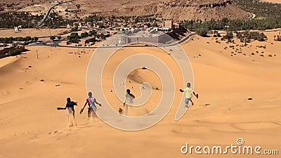 BECHAR, ALGERIA - 29 OTTOBRE 2016: i ragazzi stanno eseguendo il video di movimento lento in discesa al deserto di Taghit, Nord A archivi video