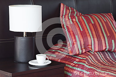 Bed , a cup of tea on the bedside table and lamp