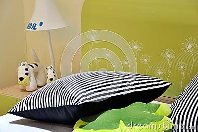 Bed en hoofdkussen in slaapkamer voor jonge geitjes