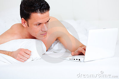 Bed lying person with computer