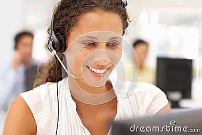 Bedrijfs vrouwen aan het werk dat een hoofdtelefoon met behulp van