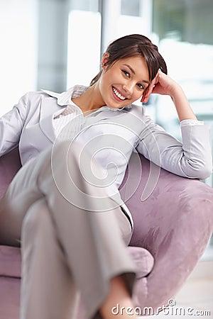 Bedrijfs vrouwenzitting comfortabel op een stoel
