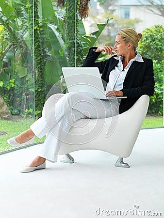 Bedrijfs vrouwenzitting op een stoel met laptop