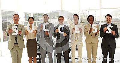 Bedrijfsmensen die brieven houden die succes spellen
