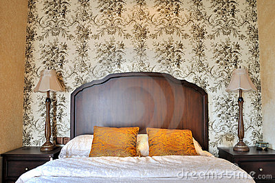 Bedroom flowery wall paper and wooden furniture