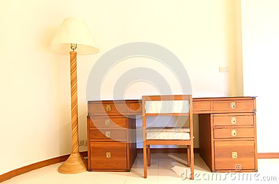 bedside table with three drawers and reading lamp