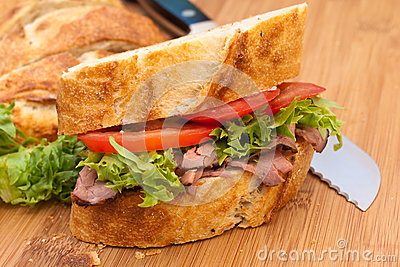 Beef sandwich on cutting board with knife.