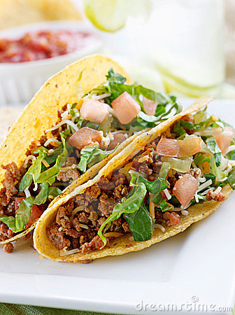 Beef tacos with lettuce cheese, tomato. and lettuc