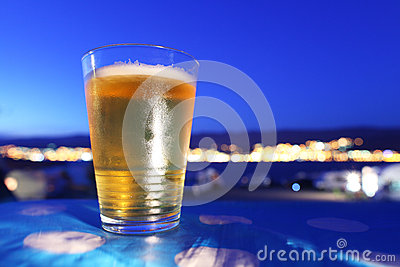 Beer glass chilled at sunset overlooking city ligh
