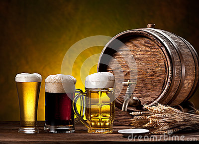 Beer glasses, old oak barrel and wheat ears. Stock Photo
