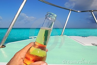 Beer on hand Caribbean in boat bow turquoise sea