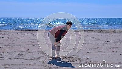 Beginner mężczyzna zatrzymujący łapać jego oddech po jogging na dennej piasek plaży zbiory wideo