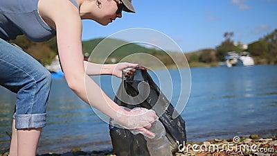 Begrip schoonmaken van het milieu Een vrouw loopt langs de rivieroever en verzamelt afval en flessen in een zak camerabeweging stock videobeelden