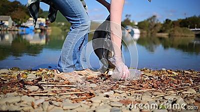 Begrip schoonmaken van het milieu Een vrouw loopt langs de rivieroever en verzamelt afval en flessen in een zak rivier op de ba stock video