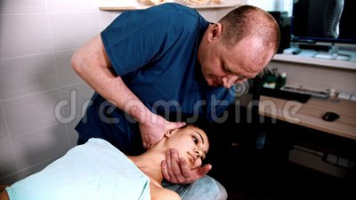 Behandeling met chiropractises - de arts heeft een vrouw die een lichte nekmassage krijgt - een kniebuiging in de nek naar de nek stock videobeelden