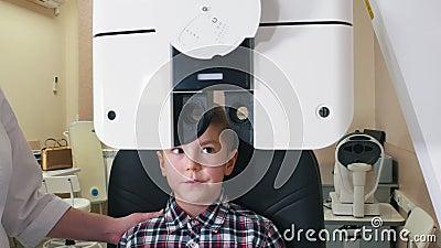 Behandeling met ftalmoloog - een kleine jongen die ogen controleert met grote apparatuur stock footage