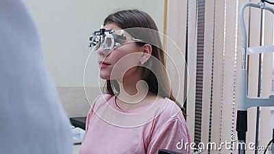 Behandeling van de oogheelkunde - een jonge vrouw die een optometrieapparaat voor een zichttest met lenzen aanbrengt - glimlachen stock video