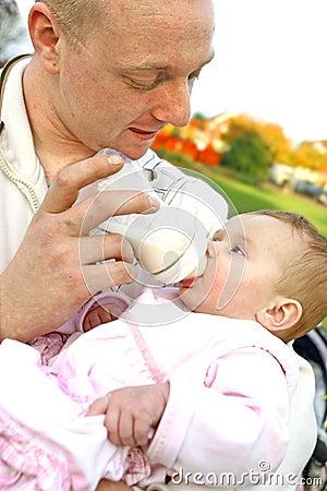 Behandla som ett barn den hans matande flickan för flaskfadern mjölkar