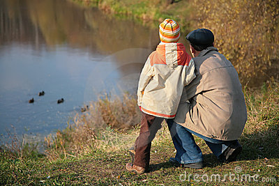 Behind grandfather with grandson look on ducks