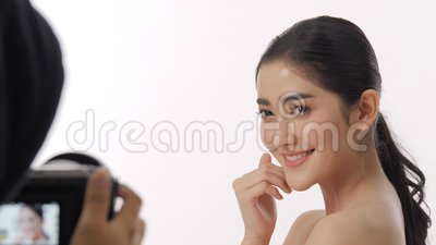 Behind the scenes shot of beautiful young asian woman model being recorded on a video camera. Behind the scenes shot of beautiful young asian woman model with stock video footage