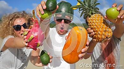 Bei giovani amici felici del vegano che hanno divertimento sciocco sulla spiaggia e che ballano con i frutti tailandesi esotici P video d archivio