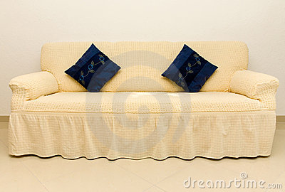 Beige couch and blue cushions.