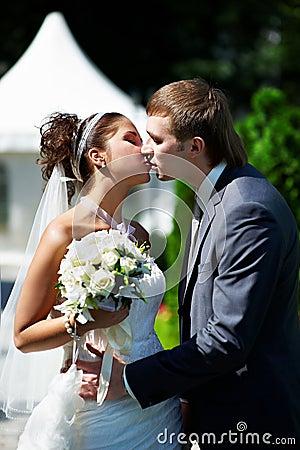 Beije a noiva e o noivo felizes na caminhada do casamento no parque