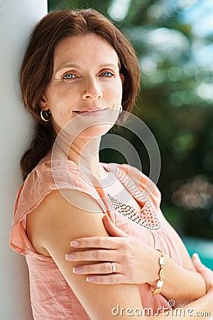 Beiläufige Frau, die draußen gegen einen Pol lächelt