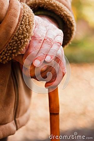Bejaarde handen die op wandelstok rusten