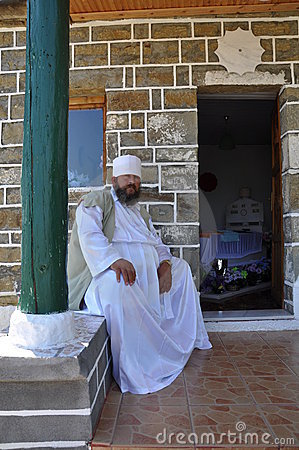 Bektashi dervish sitting on a wall of tekke Editorial Stock Photo