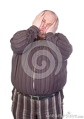 Beleibter Mann, der sein Gesicht quetscht