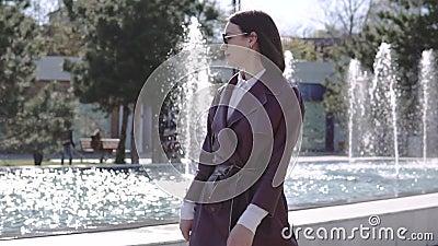 Bella donna di lusso in vestito dal rivestimento di Borgogna che cammina vicino alla fontana stock footage