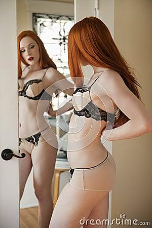 Bella giovane donna che regola la sua biancheria davanti - Ragazza davanti allo specchio ...