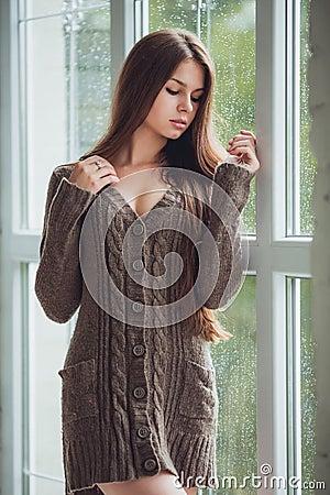 Bella giovane donna che sta da solo vicino alla finestra for Ragazza alla finestra quadro