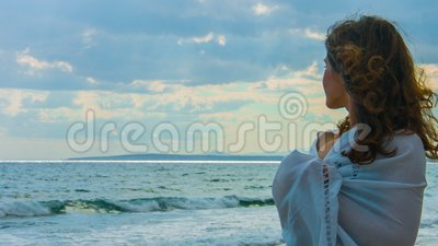 Bella giovane signora sulla spiaggia che esamina orizzonte, pensante all'amore, romanzesco video d archivio