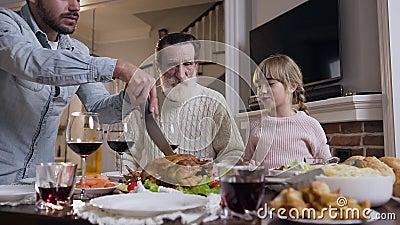 Bella ragazza che mostra a suo padre quale parte di tacchino arrosto vuole mangiare durante la festa del Ringraziamento video d archivio