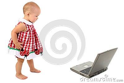 Bella ragazza del bambino che cammina verso il computer portatile