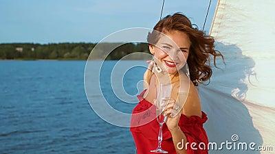 Bella ragazza vestita di rosso rilassante e che beve vino su una barca a vela archivi video