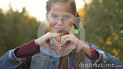 Belle adolescente qui fait du coeur avec les mains dehors Vue de la caméra Enfance banque de vidéos