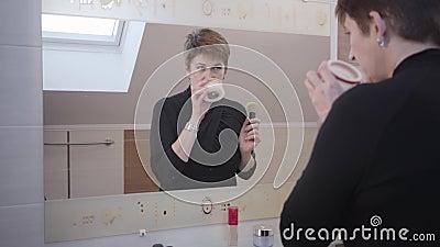 Belle brunette mature femme regardant un grand miroir et des crèmes de visage odorantes Une dame du Caucase élégante qui pose du  banque de vidéos